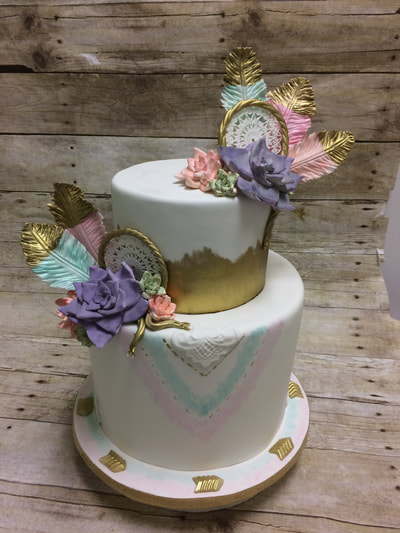 2 tier baby shower cake with gold tipped feathers.