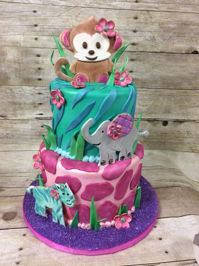 2 tier baby shower cake with animal cut outs and pink colors on bottom tier and green and blue colors on top.