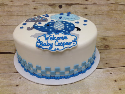 white fondant icing baby shower cake with blue spotted elephant holding an umbrella on top.