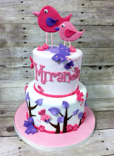 2 tier baby shower cake for a girl. Features 2 birds on top and cake is decorated with trees in colors of pink and purple.