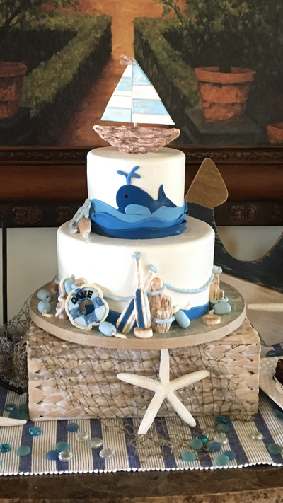 2 tier baby shower cake with nautical theme. Sail boat on top, whale in water scene on top tier and surrounding bottom tier are row boat paddles, buoys, lifesaver buoy, and nautical rope.