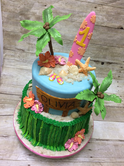 2 tier birthday cake with an Hawaiian theme. bottom tier looks like a grass skirt, top layer has a chocolate surfboard, sea shells and palm trees.