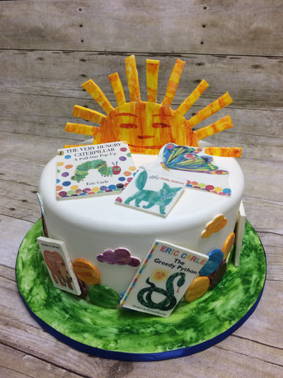 baby shower cake with sun and images from children's book.