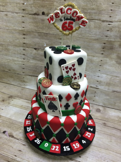 Casino theme 3 tiered birthday cake. bottom layer is surrounded by roulette wheel number slots in red black and green. 2nd tier has hearts and spade playing card, top tier is cake in a cube shape to look like a dice and topped with a chocolate Las Vegas sign.