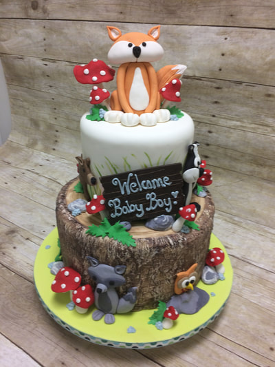 woodland themed baby shower cake with fox, owl and wolf on cake as well as bright red and white mushrooms. 2 tier with bottom tier looks like a log.