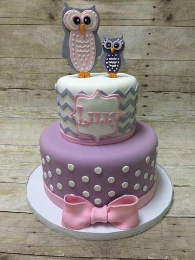 owl theme 2 tier baby shower cake. top tier has white background on cake with wavy gray lines. Bottom tier is purple background with white polka dots all finished off with a pink bow.