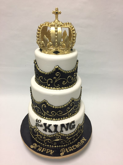 3 tier happy birthday cake with kings crown on top. black and gold scroll work.