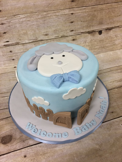 boys baby shower cake with lamb face on top and clouds and a fence around the outside of cake.