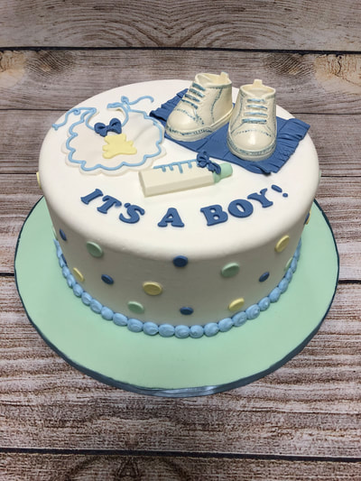 it's a boy baby shower cake. chocolate baby boots, and bib and a bottle on top. blue yellow and light blue dots around the ooutside.