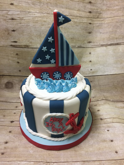 nautical theme baby shower cake. blue and white with a red white and blue sailboat on top.