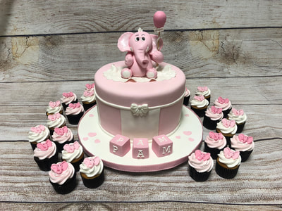 single tier baby shower cake with elephant on top and blocks in front surrounded by pink frosted cupcakes.