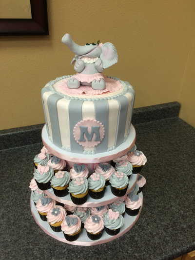 Girls baby shower cake. With baby girl elephant on top colors are pink grey and white with matching cupcakes.
