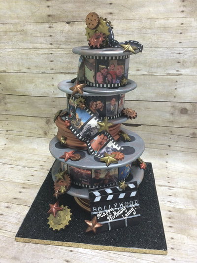 4 tier happy birthday novelty cake stacked like rolls of film. each frame showing a different picture of the family.