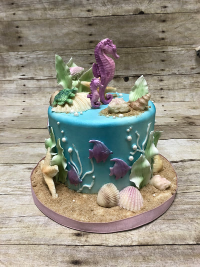 under the sea baby shower cake. blue fondant covered cake looks like the water for a sea horse on top and kelp plants, fondant fish and plants on the side of the cake and chocolate sea shells around the base.