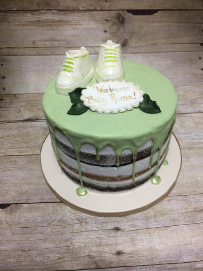 naked cake baby shower cake with light green drip icing and baby booties on top