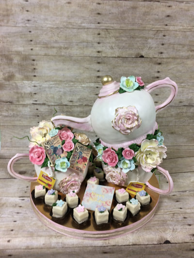 Tea party cake. With tea pot and tea cups made of cake with fondant icing. Lots of gumpaste flowers and a dozen petit fours.