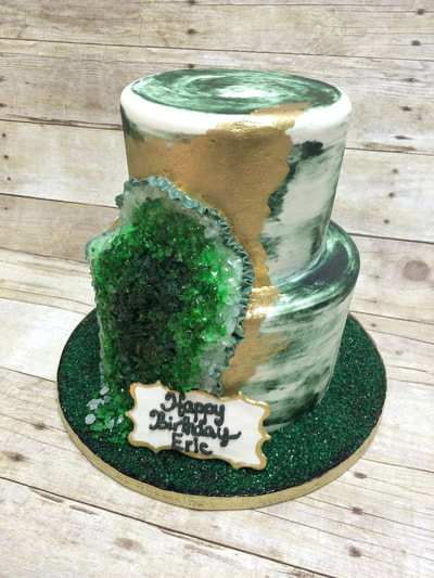 white and green naked cake with a partial geode.