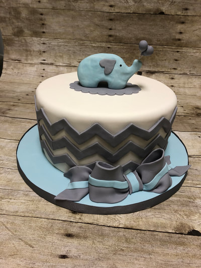 baby shower cake, light pink with blue elephant holding balloons and wavy fondant stripes around the outside.