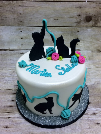Single tier cake with silhouettes of cats playing with colored fondant balls of yarn