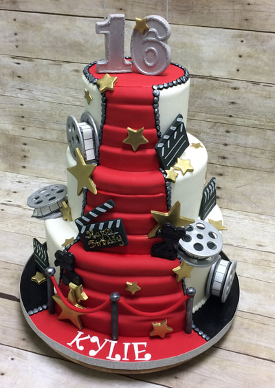 3 tier birthday cake with red carpet stairs from top to bottom and movie props all around including red velvet ropes.