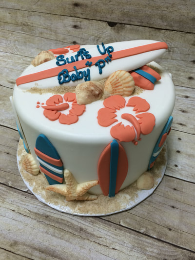 surfs up baby shower cake. single tier with chocolate surfboard on top and hibiscus flowers, chocolate sea shells.